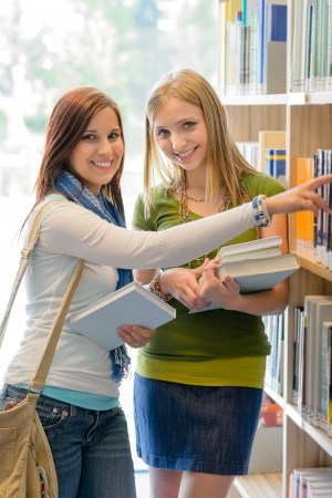 choose university: Two female teenage girls looking for book in school library Stock Photo