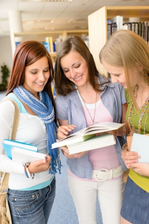 Three female high school student standing with books at library photo