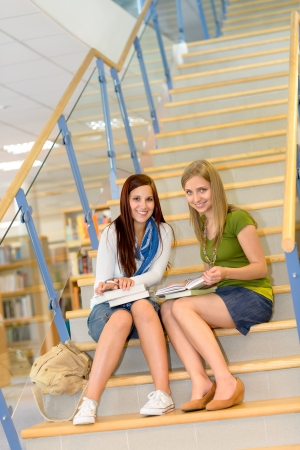 Brunette teenager with classmate studying on high school library stairs photo