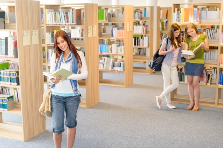three shelves: Female teenager student standing and reading book at high-school library