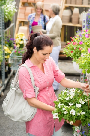 Young woman holding white surfinia flower at garden centre store photo