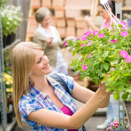 hangup: Young woman shopping flowers at market garden centre