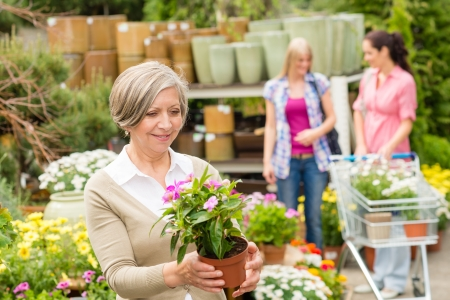 Senior lady shopping for flowers at garden centre smiling Stock Photo - 14181836