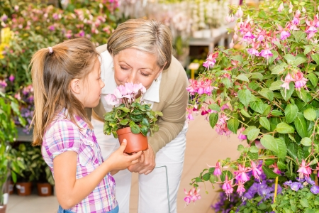 Grandmother and granddaughter holding pink potted flower at garden centre photo