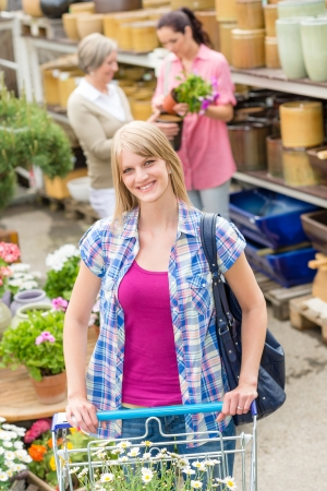 Young woman with shopping cart buying flowers at garden centre Stock Photo - 14181851