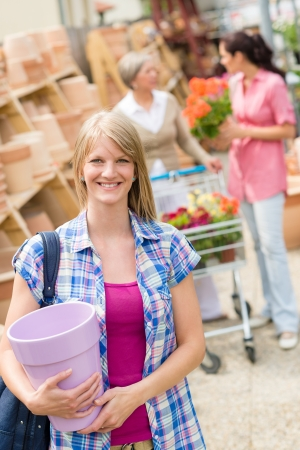 Young blonde holding flower pot at garden centre retail store Stock Photo - 14181846