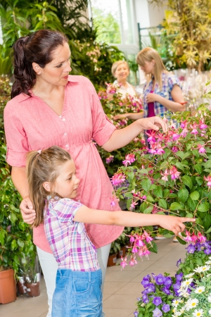 Young woman with daughter visit botanic garden shopping flowers photo