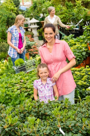 Mother and daughter shopping flowers at garden centre shop photo