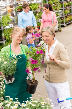 Female florist give advice to senior customer shopping for flowers photo