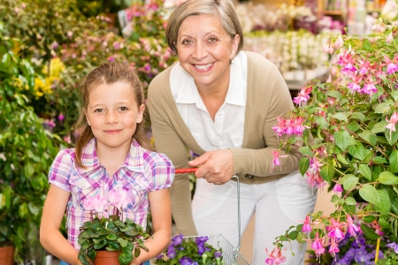 Senior woman with little girl shopping flowers at garden centre photo