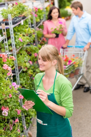 Happy florist woman make inventory at garden shopping center photo