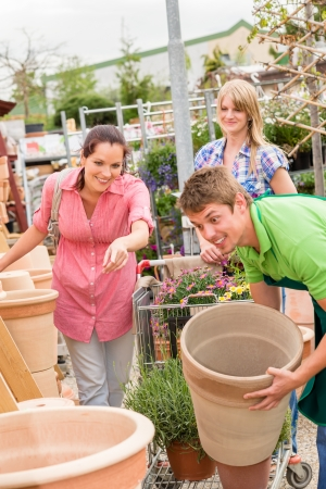 product range: Male worker at garden centre help customer choose flower pot