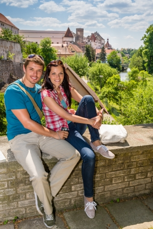 Young happy couple holiday portrait travel city sitting and smiling photo