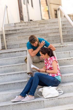 Young couple reading book guide on stairs relax outdoors photo