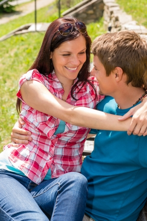 Happy young couple flirting on bench in sunny park smiling photo