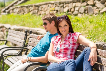 Young couple sitting on bench in park resting happy smiling photo