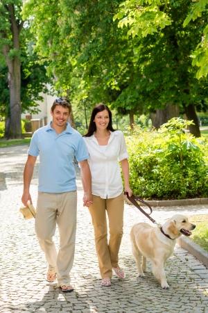 parejas caminando: Pareja en el amor caminando perro labrador en el parque d�a soleado