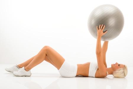 ropa deportiva: Gimnasio mujer rubia con el ejercicio de Pilates bola que reposa suelo blanco Foto de archivo