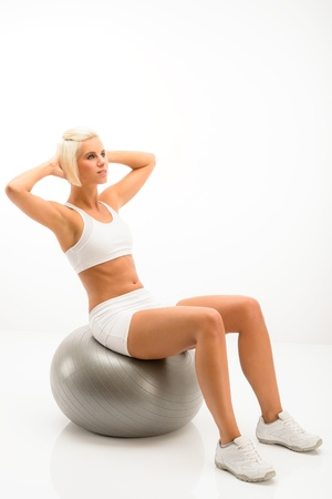 Fitness blond woman exercise on silver Pilates ball isolated white Stock Photo - 14242177