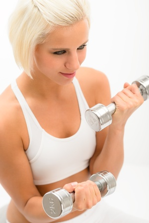triceps: Sportive blond woman exercise biceps with weights isolated on white
