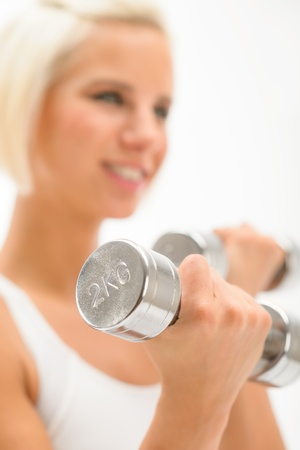Sportive blond woman exercise biceps with weights isolated on white photo