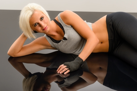 Female kickboxer laying down on black plexiglass at fitness studio photo