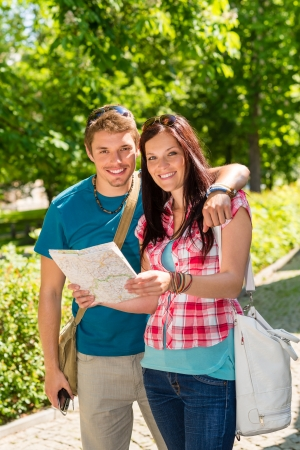 Young couple look map smiling together in sunny park photo