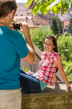 Young woman being photographed in romantic city on sunny day photo