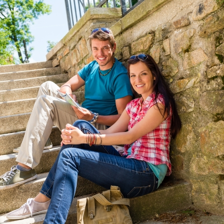 Happy young couple sitting on stairs smiling holding city map Stock Photo - 14242208