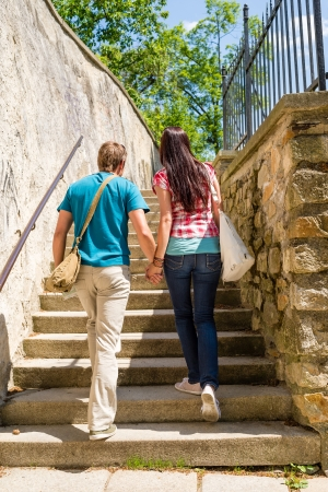 woman stairs: Young couple climbing up city stairs holding hands leisure time