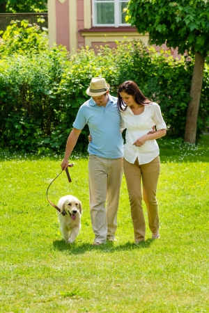 holiday pets: Happy couple walking golden retriever dog on park lawn smiling