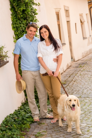 Modern couple with Labrador dog in romantic city smiling together photo