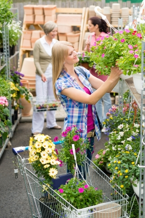 hangup: Woman shopping for flowers in garden centre plants selection Stock Photo