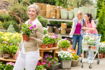 Senior lady shopping for flowers at garden centre smiling Stock Photo - 14381064