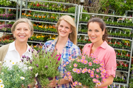 Three women holding potted flower at garden centre shop photo