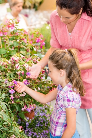 Little girl with mother looking flowers at botanic garden photo