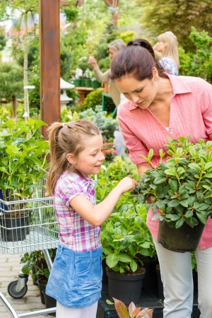Mother and daughter choosing flowers at garden centre shop photo