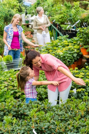 Mother and daughter choosing house plants at garden centre shop photo