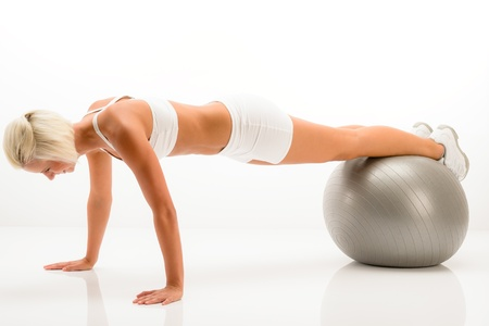 pushups: Sportive woman doing pushup exercise on fitness ball white background