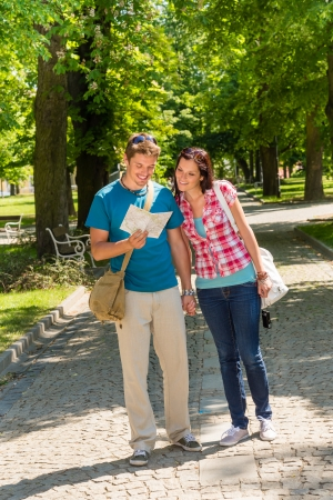 Young couple looking at map in park happy tourists holiday photo