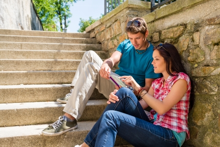 Young couple looking city map sunny day sitting stairs together Stock Photo - 14381148