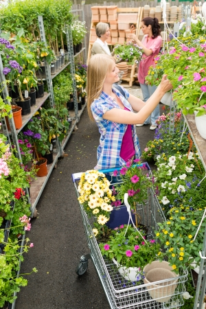 sowbread: Woman shopping for flowers in garden centre plants selection Stock Photo