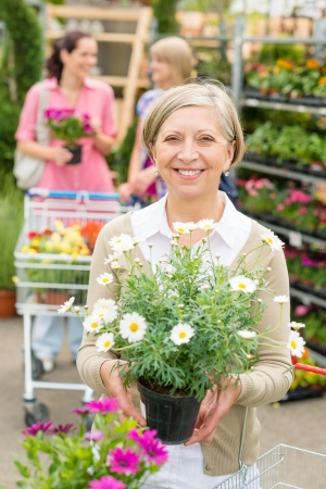 Senior lady shopping for flowers at garden centre smiling photo