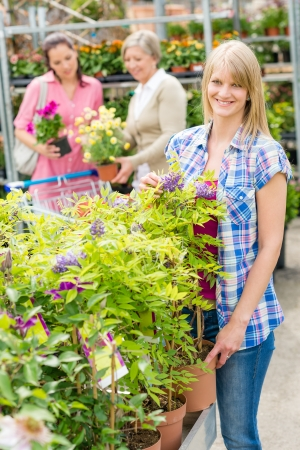 Smiling woman at garden centre shopping for house plants photo