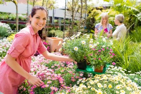 Smiling florist arranging flower pots in garden center greenhouse store photo
