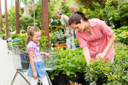 Little girl with mum shopping flowers plant at garden centre photo