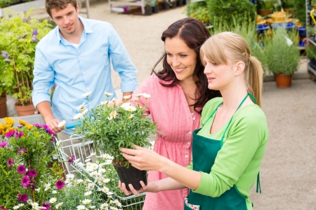 selling service smile: Florist at garden centre selling potted flowers to young couple