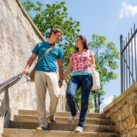 subiendo escaleras: Feliz pareja cogidos de la mano buscando el uno al otro sonriendo Foto de archivo
