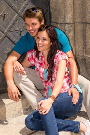 Young couple tourist sitting on doorstep smiling sunny day photo