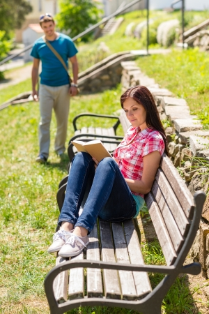 coming together: Young woman reading book on bench man coming towards her Stock Photo